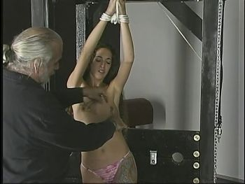 A-cup brunette with arms roped above her head stands while dude clamps her tits
